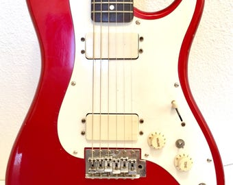 """Cute Candy Apple Red Vintage Hondo """"bullet"""" strat with case and vintage guitar book"""
