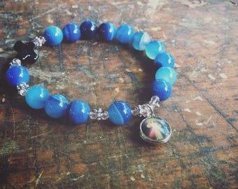 Blue beaded elastic stretch rosary bracelet with charm and black cross bead