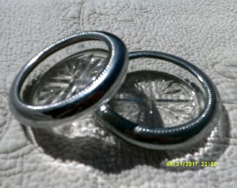 Two round glass coasters with silver rims