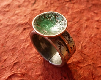 Copper disc partially enamelled green mounted on an open worked copper and aluminum ring ring