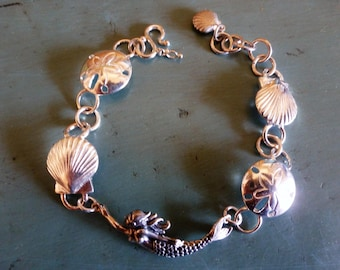Mermaid's Swag Bracelet is a sterling silver treasure trove of beautiful shells and their mermaid collector - collect it yourself!