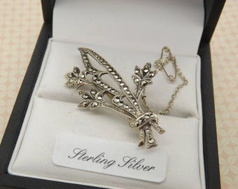 A super period 925 fine silver flower spray vintage jewelry brooch made in an openwork design set with sparkly marcasites faceted stones