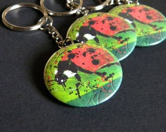 Keychain with a ladybug on green background