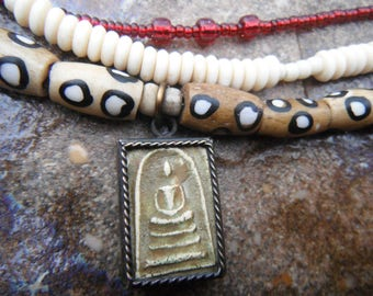 Thai Buddha Amulet and Batik Bone bracelet with carved bone skull, bone spacers, and red glass beads