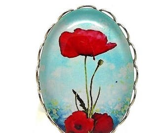 Ring cabochon silver poppy on blue background