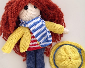 Red crochet doll in a yellow raincoat