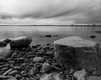 Fine art photographic print of dark sky and icy rocks along the Great Lake Ontario wild shore. Placid water and late autumn sky scene.