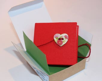 Note book in red, blank, square with plaited wrap around fastening and heart button in presentation box