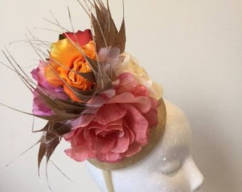 Cream fascinator with various flowers and gold tip feathers on a headband!