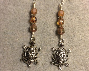 Silver tortoise charm dangle earrings adorned with tan and amber Czech glass beads.