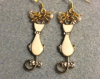 White enamel and rhinestone long-tailed cat charm earrings adorned with tiny dangling white, gold, and clear Chinese crystal beads.