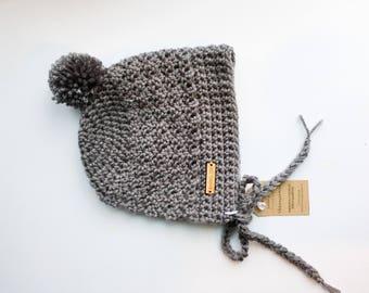 Crochet baby bonnet with pom pom
