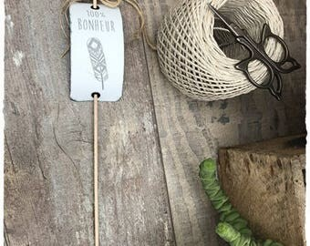 A pretty white metal tag with engraving on wooden stick