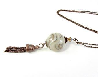 Sautoir grosse perle blanche et beige, et son pompon cuivré