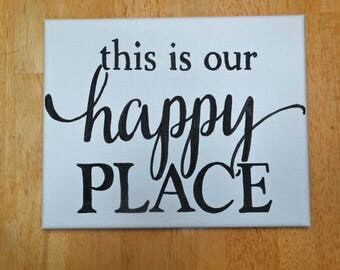 """Hand painted canvas sign reads: """"This is our happy place"""" typography"""