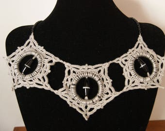 Necklace is crocheted with grey cotton thread, beads