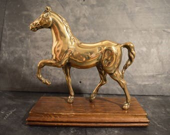 Brass horse on wooden plinth