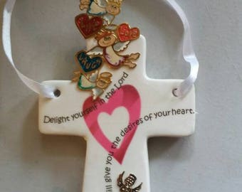 Whimsical ceramic cross decorated with tiny angels.