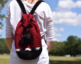 Black and burgundy crochet backpack with fuzzballs