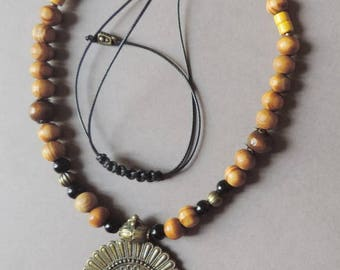 Small bronze breastplate necklace on wood