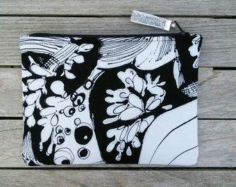 Makeup bag, pouch, black, silver and white graphic fabric. Black lining. White faux leather pocket.