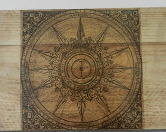 Old compass on raw wood plank wall decor, rose