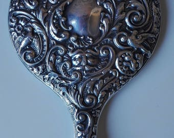 Silver Embossed hand mirror. Late nineteenth century