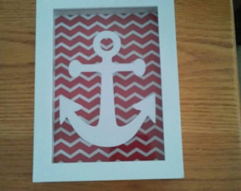 Shadow box displaying nautical vinyl anchor. Background red an white chevron. Measures 5x7
