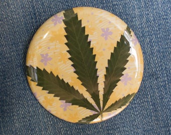 Pressed Cannabis Leaf Button On Orange & Purple Background