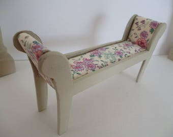 A miniature Shabby Chic Window seat with floral seat cover in one 12th scale