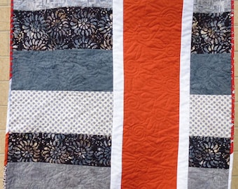 Gray and white crib or lap quilt, with an orange vertical stripe