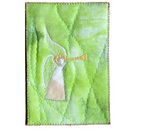 Trumpet angel on green fabric postcard