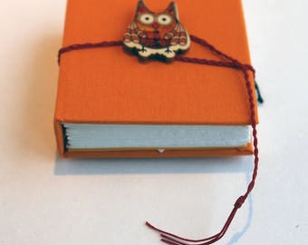 Pocket notebook, Orange  hardback , blank white cartridge  inside with  hardback cover, owl button and plaited tie fastening