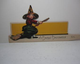 Colorful Die cut unused 1920's Hallmark Halloween Place card little girl witch on her broom wearing a jack o'lantern decorated witches hat