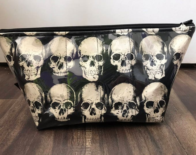 Zippered makeup bag in a skull fabric with clear vinyl top layer