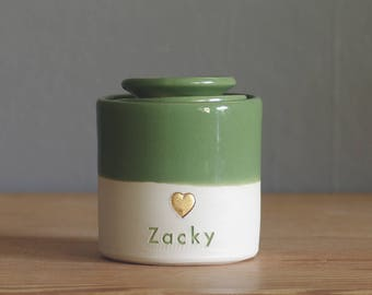 custom urn. ceramic lid, straight shaped urn with custom stamp. modern simple urn for ashes. green and gold urn shown.