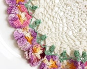 vintage handmade crocheted round mildly stained white doily with multicolored decorative edging of lilac seafoam orange-yellow