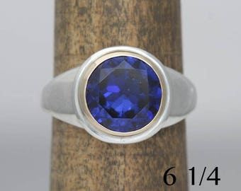 Saphire ring, size 6 1/4 mixed metal ring with a manmade sapphire,  #381.