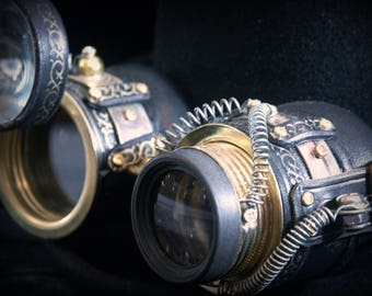 Steampunk goggles in black leather and brass with monocle-style ocular, moveable loupe and embossed gold tone decoration.