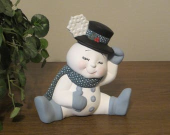 Sitting snowman with snowflake on hat