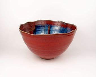 Medium bowl in rich raspberry red with sky blue accent and wavy rim