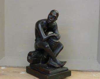 Statue of man on log playing drum