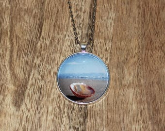 Pendant necklace featuring a photograph of an orange shell on the beach