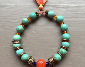 Turquoise beaded bracelet accented with orange agate bead, bronze findings and orange tassel on a strong stretch cord.