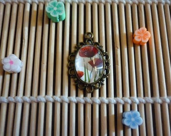 Serrated and fluted brass pendant, cabochon oval glass poppies on white background.