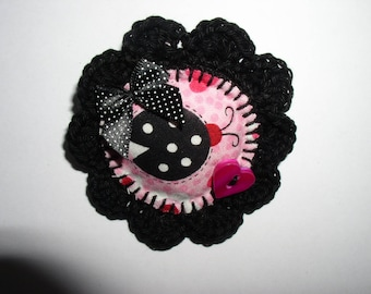 brooch is crochet and fabric printed with button and bow