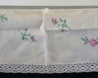 Beautiful vintage table runner featuring floral crosstitch needlework and lacey crochet edging