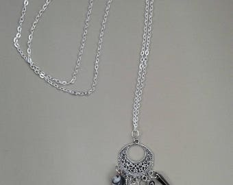 Long necklace on thin silver chain with different charms.