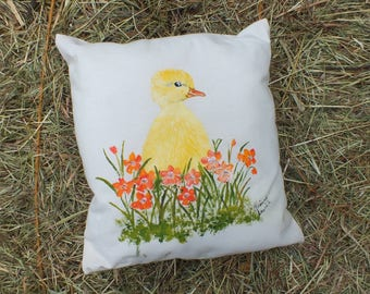 sweet little duck painted on a small off-white pillow-