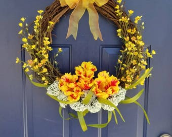 Designer spring and summer floral wreath. Yellow and red tulips w/ white flower tufts and yellow/orange accent flowers and greenery w/ bow